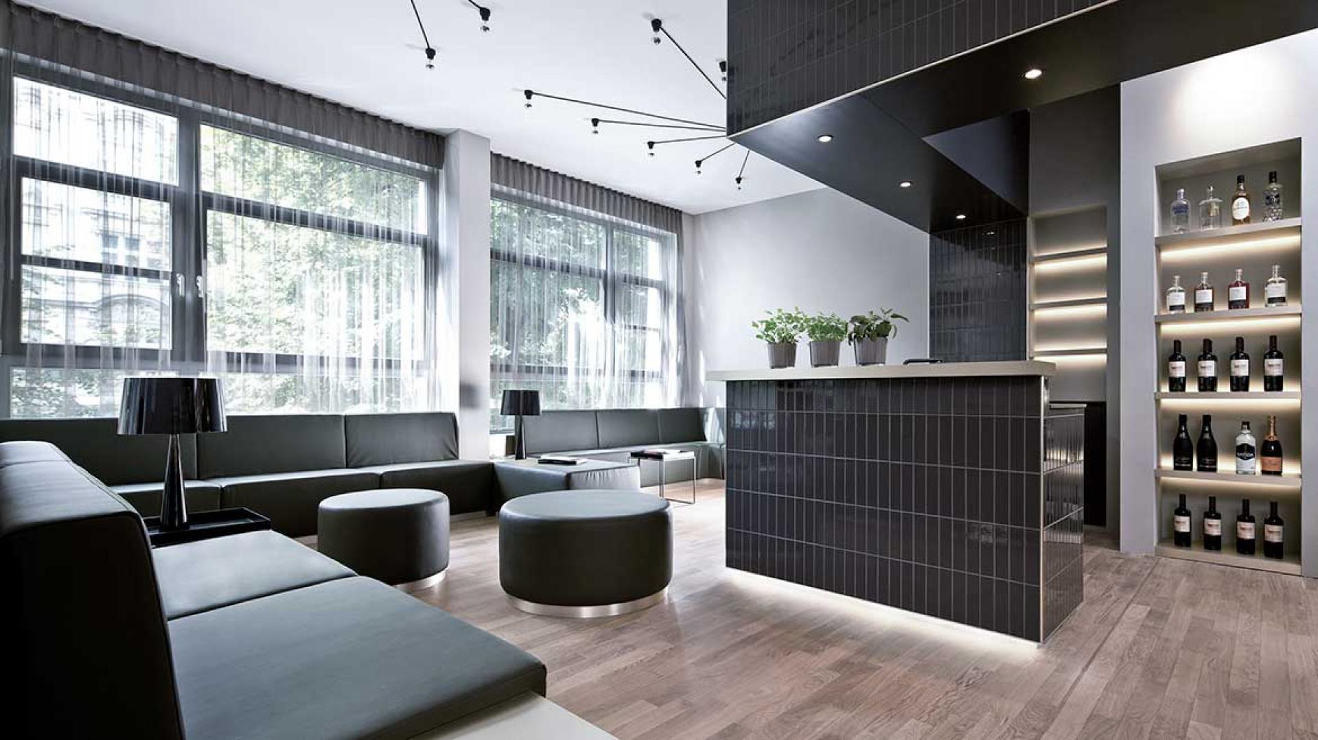 Zlokalizowana w kubiku obszerna kuchnia otwiera się na elegancki hol, w którym zlokalizowano komplet mebli wypoczynkowych. Komponują się one kolorystycznie z ciemnymi kaflami położonymi wokół kuchni. Surową kolorystykę przełamuje parkiet w ciepłym kolorze naturalnego drewna. Fot. www.suite030.com.
