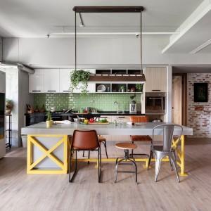 Mieszkanie jest przestronne i bardzo przytulne. Mimo industrialnego charakteru, zastosowano w nim ciepłe barwy, które nadają wnętrzu domowego wyrazu: jesienne żółcie, zgniła zieleń i naturalne drewno tworzą wspólnie przytulną atmosferę. Fot. Hey! Cheese.