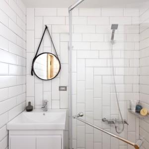 Łazienka kontrastuje z resztą mieszkania. Wykończona niemal całkowicie na biało, została ocieplona jedynie drewnianą podłogą. Ciekawym akcentem dekoracyjnym są fantazyjnie ułożone białe kafle. Fot. Hey! Cheese.