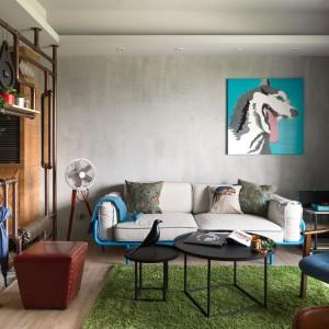 Kącik wypoczynkowy to królestwo uporządkowanego eklektyzmu. Szary tynk na ścianie i przepierzenie wykonane z metalowych rur nadają mu industrialnego charakteru, podczas gdy kolorowe akcenty ożywiają przestrzeń. Klasyczne meble połączono z nowoczesnymi, a całość wieńczy kolorowa grafika na ścianie. Fot. Hey! Cheese.