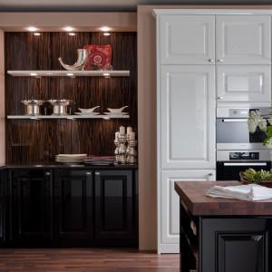 Eleganckie połączenie czarnych i białych frontów zwieńczono pięknym czekoladowym blatem. Frezowane  fronty szafek wykończono na połysk, przez co kuchnia zyskuje delikatnie nowoczesnych charakter. Fot. Leicht, kolekcja Elegance.