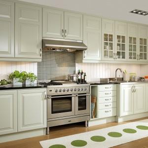Urokliwe meble w kolorze bladej zieleni nadają tej kuchni niepowtarzalny charakter.  Z klasycznymi meblami komponuje się deska na ścianie i mozaika nad płyta kuchenną. Fot. Bollingslov, kolekcja Meny.