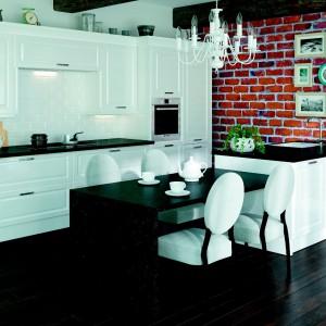Piękne, klasyczne, białe meble, zwieńczone czarnym kontrastującym blatem. Wraz z miękkimi ozdobnymi krzesłami i francuskim żyrandolem tworzą kompozycję w stylu glamour. Fot. Atlas Meble, kolekcja Maria.