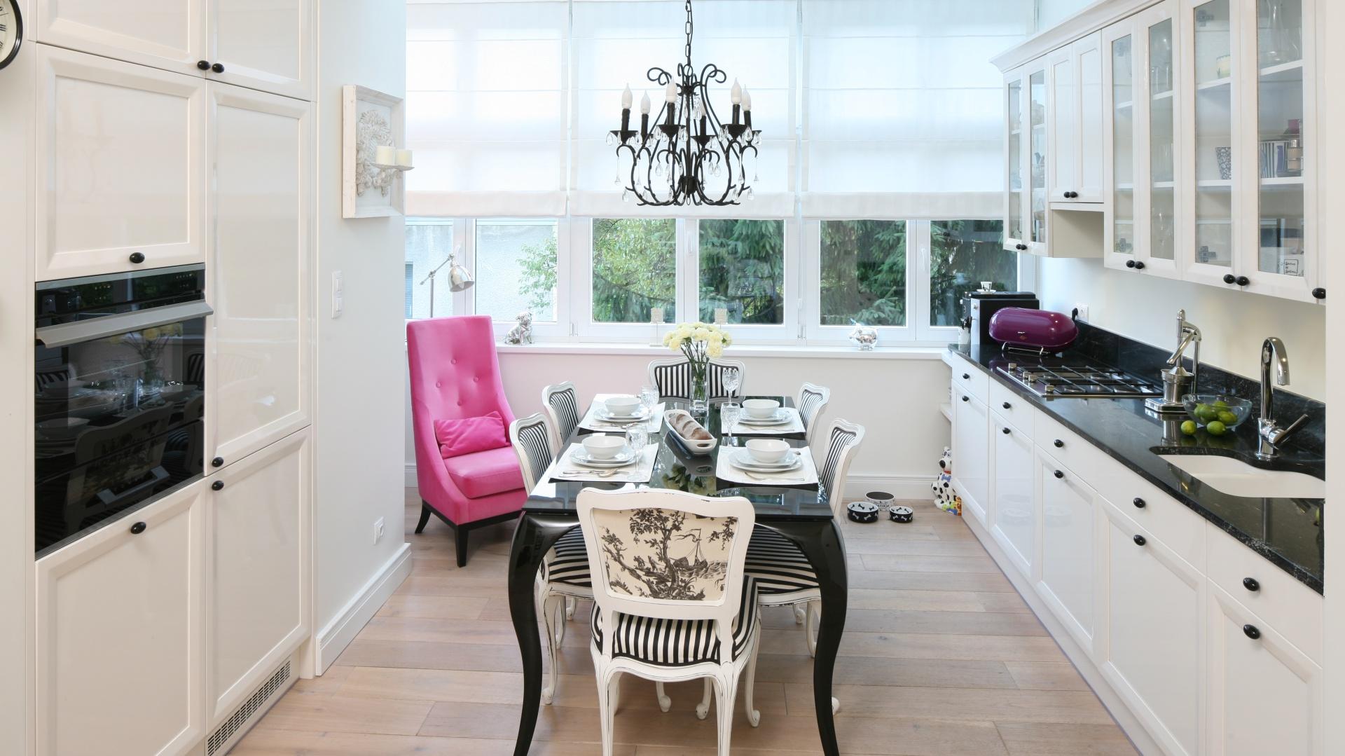 Czarny jest również francuski żyrandol i stylizowany stół, do którego dobrano biało-czarne ozdobne krzesła. Projekt: Małgorzata Galewska. Fot. Bartosz Jarosz.