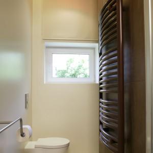 Ściana po lewej od wejścia, z długim relingiem, zakończonym uchwytem na papier, wykończona została farbą łazienkową w kolorze beżowym. Pod kolor ściany dobrano podłogowe płytki gresowe. Fot. Bartosz Jarosz.
