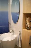 W tej łazience dominuje biel oraz niebieska toń wody. Wrażenie przytulności i ciepła daje zabudowa meblowa imitująca jasny dąb.
