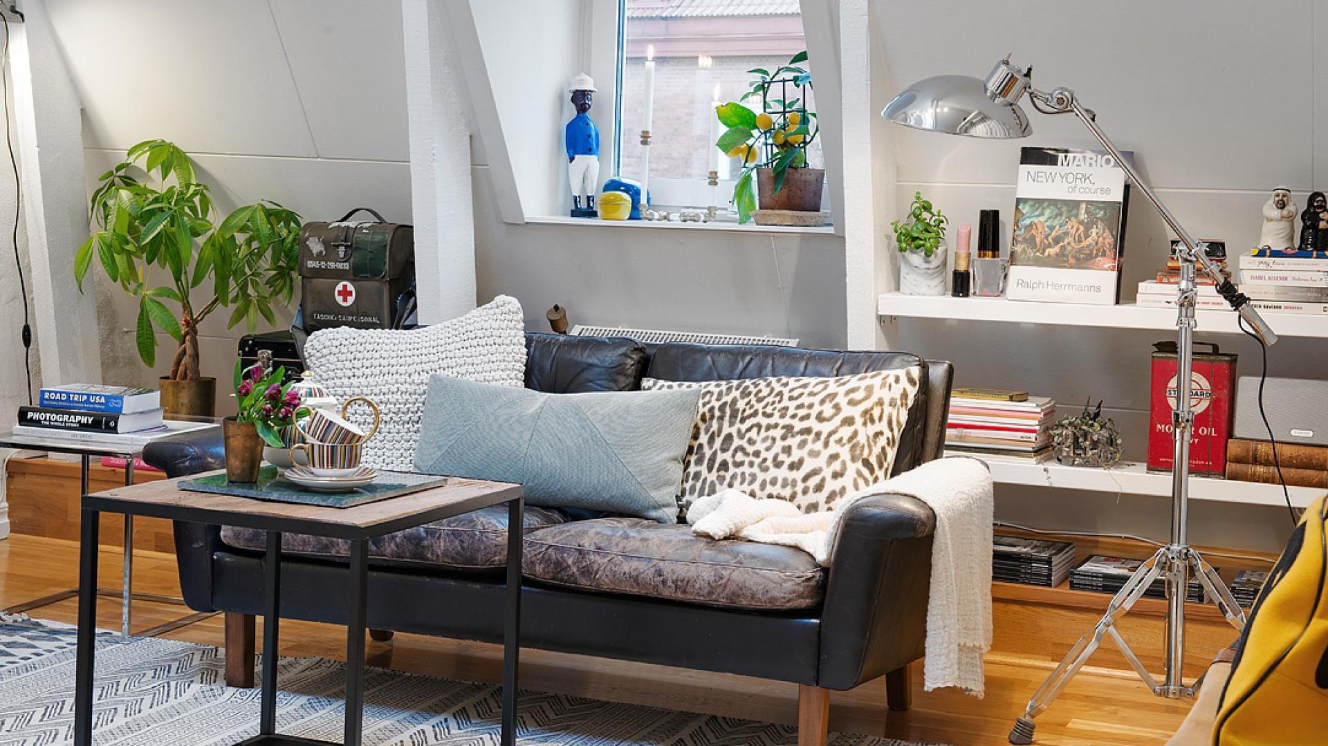 Salon stanowi bardzo przytulny kącik wypoczynkowy i nowoczesny, metalowy stolik kawowy. Różnobarwne, wzorzyste tekstylia nadają przestrzeni domowego klimatu, a lampa stojąca nawiązuje do stylistyki loftowej. Fot. Alvhem Makleri.