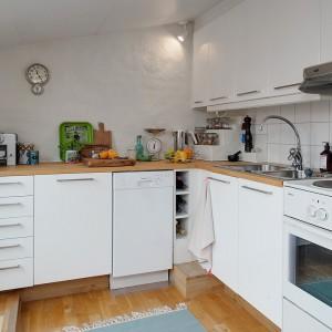 W kuchni dominuje kolor biały, ocieplony drewnem. Białe meble i płytki na powierzchnią roboczą zestawiono z drewnianym parkietem na podłodze i drewnianym blatem w takim samym kolorze. Fot. Alvhem Makleri.