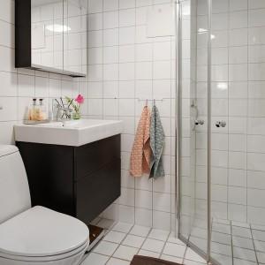 Czarno-biała niewielka łazienka jest utrzymana w prostej, współczesnej stylistyce. Ostre linie, geometryczne kształty i monochromatyczna kolorystyka nadają jej nowoczesnego wyrazu. Fot. Alvhem Makleri.