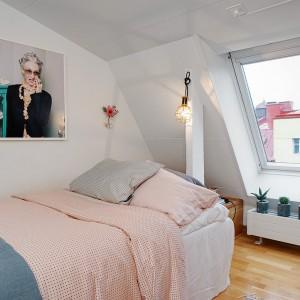 W przytulnej sypialni zagospodarowano każdy skrawek przestrzeni. Miejsce za łóżkiem, bezpośrednio pod skosami zagospodarowano na niewielki schowek. Pod oknem, sięgającym niemal do samej podłogi usytuowano niewielki grzejnik. Fot. Alvhem Makleri.
