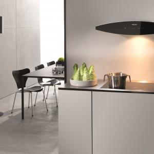 Dekoracyjny okap DA 7090 W. Wykonany z czarnego szkła oraz elementów z blachy ocynkowanej malowanych na biało. Minimalistyczna nowoczesna stylistyka pasuje idealnie do nowoczesnych wnętrz i nadaje im eleganckiego charakteru. Fot. Miele.
