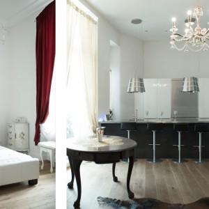 Wnętrze w stylu glamour uzupełniono nowoczesnymi akcentami. Oświetlenie nad półwyspem czy zabudowę kuchenną utrzymano we współczesnej stylistyce. Fot. www.suite030.com.