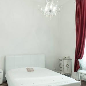 Biała, świeża sypialnia stanowi przeciwwagę dla intensywnych różów i czerni w poprzednim pomieszczeniu. Dekorację tworzą tutaj stylizowane jasne meble i francuski żyrandol. Całość ożywiono bordowymi zasłonami. Fot. www.suite30.com.