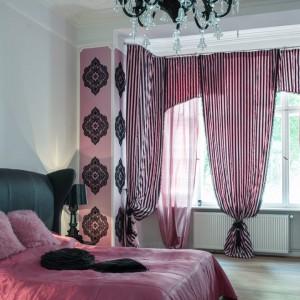 W dużej, przestronnej sypialni wzrok postawiono na intensywne dekoracje. Róż w odcieniu fuksji na łóżku i wokół okien komponuje się z nasyconą czernią i wzorzystymi formami. Całość tonują białe ściany i jasna podłoga. Fot. www.suite030.com.