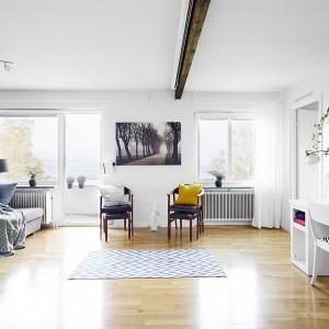 Przestronny salon umownie podzielono na strefę do wypoczynku i kącik do pracy. Granicę między nimi wydziela poprowadzona w poprzek pomieszczenia belka stropowa oraz zlokalizowane w centrum dwa stylizowane krzesła i jesienna fotografia na ścianie.