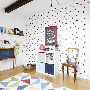 Jasne wnętrze pokoju dziecięcego ożywia kolorowy dywan w geometryczne wzory i tapeta we wzór polka dotts. Fot. Vastanhem.