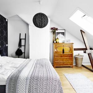 Sypialnię ocieplają brązowe elementy w postaci stylizowanej komody, drewnianego parkietu i widocznych belek pod skosami. Fot. Vastanhem.