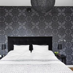 Ścianę za łóżkiem pokryto piękną wzorzystą tapetą. Komponuje się z nią czarny pikowany zagłówek i równie czarne stoliki nocne i nocne lampki. Na uwagę zasługuje garderoba, do której drzwi schowano w... ścianie, niczym tajemne przejście do sekretnego schowka ze skarbami. Fot. Vastanhem.