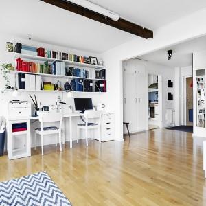 W przestronnym salonie urządzono również przestrzeń do pracy. Na jednej ze ścian zlokalizowano praktyczne półki, służące za biblioteczkę oraz biurko. Wszystko w bieli, którą ożywiają sprzęty i książki na półkach. Fot. Vastanhem.