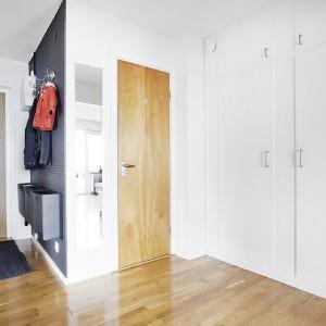 Po wejściu do mieszkania wita nas jasny hol z ciemniejszym akcentem w kąciku do wieszania ubrań. Wnętrze ociepla drewniany parkiet i dopasowane pod podłogę drzwi. Fot. Vastanhem.