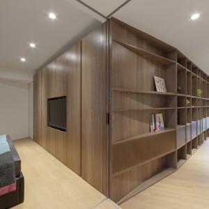 """Długa ściana, w całości pokryta drewnianym panelem, na którym zlokalizowano masę półek, prowadzi od jadalni aż do sypialni, gdzie """"skręca"""" i przechodzi płynnie w panel telewizyjny i szafę na ubrania. Fot. KC Design Studio."""