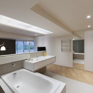 Odważne i kreatywne potraktowanie przestrzeni łazienki i sypialni. Brak lustra nad umywalką rekompensuje duże lustro na ścianie łączącej pomieszczenia. Fot. KC Design Studio.