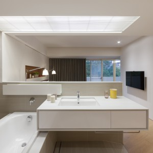 Widok z łazienki na sypialnię. Na niskiej ściance działowej zlokalizowano wannę i umywalkę. Zamiast tradycyjnie występującego w miejscu nad umywalką lustra znajdziemy tutaj wolną przestrzeń. Domownicy mogą komfortowo rozmawiać ze sobą, przebywając w dwóch pomieszczeniach. Fot. KC Design Studio.