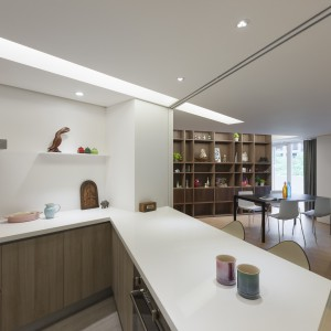 Wewnątrz kuchni dominuje biel - na ścianie i blacie kuchennym, oraz drewno w odcieniu kawy z mlekiem na frontach szafek. Z pomieszczenia rozciąga się widok na jadalnię i salon. Fot. KC Design Studio.