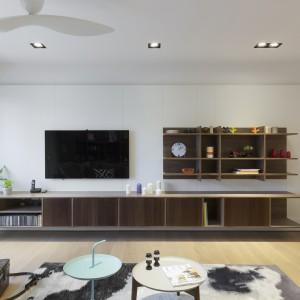 Na ścianie w salonie prostopadłej do kącika wypoczynkowego powieszono telewizor i kilka praktycznych półek, zamocowanych na drewnianej płycie. Wzdłuż niemal całego pomieszczenia poprowadzono długą, podwieszaną szafkę RTV. Fot. KC Design Studio.