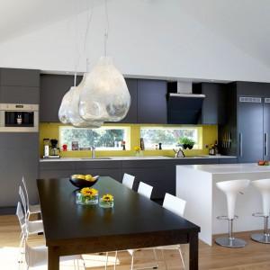 Fot. Ciemny stół jadalniany kontrastuje efektownie z białymi krzesłami i wyspą-barem. Fot. Ballingslov, linia Solid.