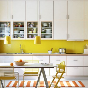 Energetyzująca przestrzeń kuchni i jadalni zapewnia codzienną dawkę energii. Lekki stół jadalniany komponuje się z prostymi frontami szafek. Żółte krzesła nawiązują kolorem do ściany nad blatem i lamp wiszących nad stołem. Fot. Ballingslov, linia Decor.