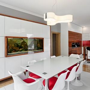 Nowoczesna kuchnia wykończona na połysk komponuje się kolorystycznie z zabudową i stołem w strefie jadalni. Czerwone siedzenia krzeseł korespondują z czerwonymi płytkami nad blatem kuchennym. Fot. Atlas Meble, linia Oktawia Listwowy.
