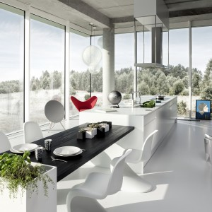 Piękna nowoczesna kuchnia z jadalnią, bazująca na efektownych kontrastach. Szafki i blat stołu utrzymano w kolorze ciemnego, egzotycznego drewna, podczas gdy wyspa i krzesła są śnieżnobiałe. Niebanalnym rozwiązaniem jest połączenie wyspy ze stołem jadalnianym. Fot. ZAJC Kuchnie, Kuchnia Z3/006.