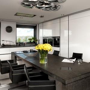Czarno-biała kuchnia z masywnym stołem, którego nogi stanowią monolityczna płyta oraz...wyspa kuchenna. Połączenie białej wysokiej zabudowy na połysk i oryginalnego stołu daje kapitalny efekt! Fot. ZAJC kuchnie, Kuchnia Z1/025.
