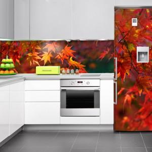 Kuchnia w pięknych, jesiennych barwach. Motyw z czerwieniejącymi się liśćmi nad blatem kuchennym dopasowano do kolorowej naklejki na lodówce. Fot. DecoMania.pl.