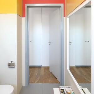 Niewielkie i wąskie pomieszczenie ożywiają kolory, a a optycznie powiększają duże lustra umieszczone na przeciw siebie. Projekt: Konrad Grodziński. Fot. Bartosz Jarosz.