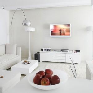 W skąpanym w bieli salonie nie tylko ściana, ale i sam telewizor musiał być biały. Takie rozwiązanie pozwoliło zachować lekkość i świeżość całej aranżacji. Projekt: Piotr Gierłatowski. Fot. Bartosz Jarosz.