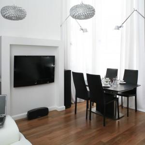 W eleganckim wnętrzu o minimalistycznej stylistyce duży telewizor zawieszono na ścianie między jadalnią a salonem. Projekt: Michał Mikołajczak. Fot. Bartosz Jarosz.