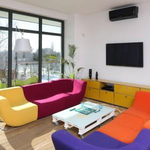W wielokolorowym salonie z ogromnymi oknami pozostała właściwie tylko jedna ściana, na której telewizor mógł się dobrze prezentować. Zawieszony został nad żółtą szafką rtv. Projekt: Konrad Grodziński. Fot. Bartosz Jarosz.
