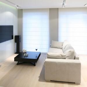W niewielkim mieszkaniu duży telewizor zawieszono w centralnym miejscu na ścianie naprzeciw zabudowy kuchennej. Projekt: Monika i Adam Bronikowscy. Fot. Bartosz Jarosz.