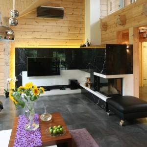 W domu wykonanym z bali, w którym drewno ciągle pracuje, nie można było zawiesić telewizora bezpośrednio na ścianie. Dlatego zdecydowano się na dobudowanie specjalnej ścianki, którą obłożono kamienie, Projekt: Tomasz Motylewski, Marek Bernatowicz. Fot. Bartosz Jarosz.