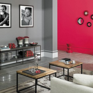 Neutralna szarość w salonie pozwoli zbudować klasyczną aranżację. Skontrastowana z czerwienią prezentuje się wyśmienicie. Fot. Tikkurila.