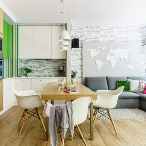 Salon, kuchnia i jadalnia tworzą wspólną otwartą open space. Przestrzeń spajają jednorodna podłoga i fototapeta na ścianie. Za narożnikiem zlokalizowano panel 3D przedstawiający mapę świata - w każdym elemencie aranżacji odczuwa się międzynarodowy charakter. Projekt: Saje Architekci, współpraca Aleksandra Nowakowska. Fot. foto&mohito.