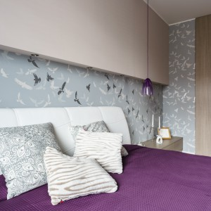 W sypialni dominują szarości i beże, ożywione fioletowymi akcentami w postaci tkanin na łóżku i wiszących lamp, pełniących funkcję lampek nocnych. Projekt: Saje Architekci, współpraca Aleksandra Nowakowska. Fot. foto&mohito.