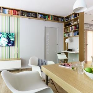 """Otwartą przestrzeń salonu, kuchni i jadalni wykorzystano do maksimum. W rogu pomieszczenia udało się urządzić niewielki kącik do pracy, nad którym zamontowano zabudowę z półkami, pełniącymi rolę biblioteczki. Poprowadzona została wzdłuż ściany aż pod sam sufit, gdzie przechodzi na prostopadłą ścianę i dalej """"idzie"""" sufitem aż nad strefę z telewizorem. Projekt: Saje Architekci, współpraca Aleksandra Nowakowska. Fot. foto&mohito."""