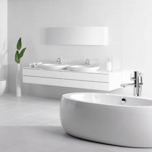Na tle białej, minimalistycznej aranżacji wyróżnia się designerska armatura: baterie umywalkowe i wannowa pochodzą z kolekcji Il Bagno Alessi One by Oras. Fot. Oras.