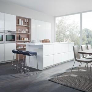 Gładkie, białe powierzchnie wykończone na połysk ociepla wstawka z drewna, zlokalizowana w centrum zabudowy kuchennej. Dzięki temu zabiegowi, kuchnia jest jednocześnie nowoczesna i minimalistyczna, ale nie brak jej domowego klimatu. Fot. Leicht, kolekcja Orlando-K.