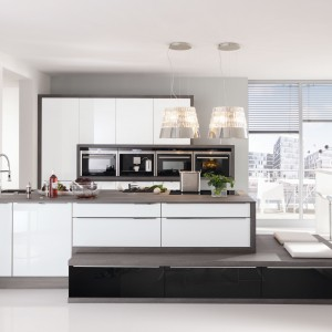 Zestaw mebli kuchennych z frontami z bezpiecznego szkła. Praktyczne i estetyczne rozwiązanie do nowoczesnych kuchni. Połyskująca biel pięknie komponuje się z brązowym obramowaniem. Fot. Nolte Kuchen, kolekcja Glas Tec Plus.