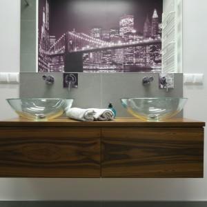 Grafika została umieszczona na ścianie obok sedesu, naprzeciwko umywalek, dlatego efektownie odbija się w lustrze nad nimi.  Projekt: Katarzyna Merta-Korzniakow. Fot. Bartosz Jarosz .