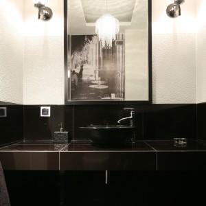 Fototapet, która odbija się także w lustrze zapewnia toalecie reprezentacyjny, nieco klubowy klimat. Projekt: Karolina i Artur Urban. Fot. Bartosz Jarosz.